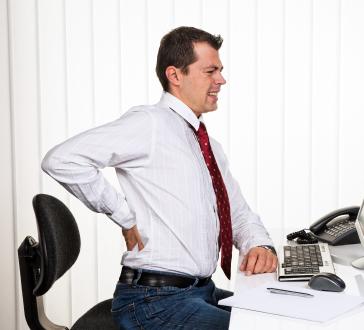 Mann im Büro bei Computer und Rücken Schmerzen